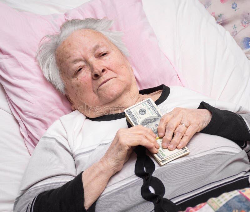 Alte Frau, die im Bett liegt und Dollarbargeld hält stockbilder