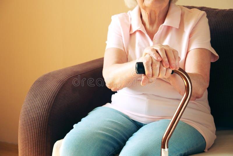 Alte Frau, die mit seinen Händen auf einem Spazierstock sitzt Älteres Leutegesundheitswesen lizenzfreie stockbilder