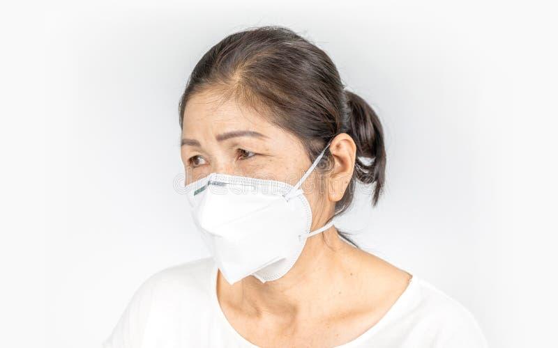 Alte Frau, die N95 Gesichtsmaske für gesundes trägt stockbild