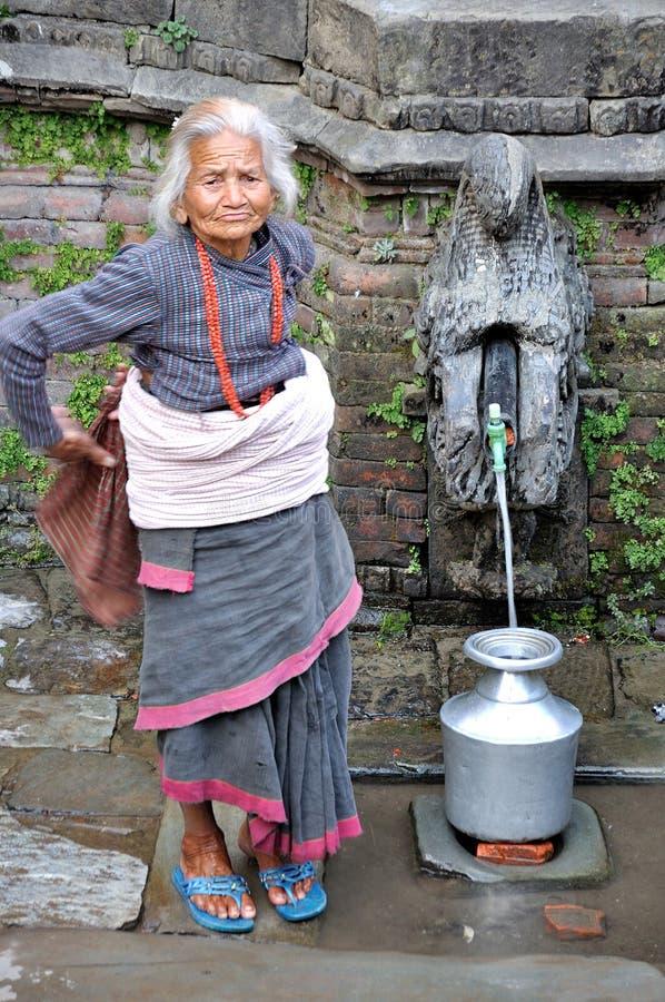 Alte Frau, die Wasser erhält stockfotografie