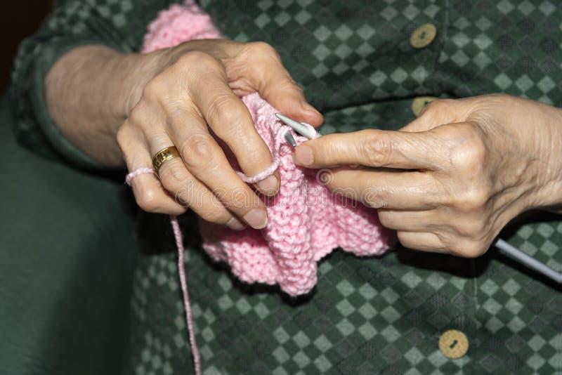 Alte Frau, die zu Hause strickt lizenzfreie stockfotografie