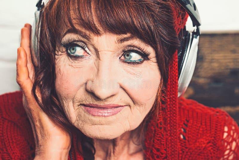 Alte Frau hören Musik in den Kopfhörern stockbilder