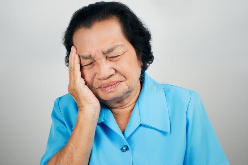 Alte Frau haben Kopfschmerzen stockbilder