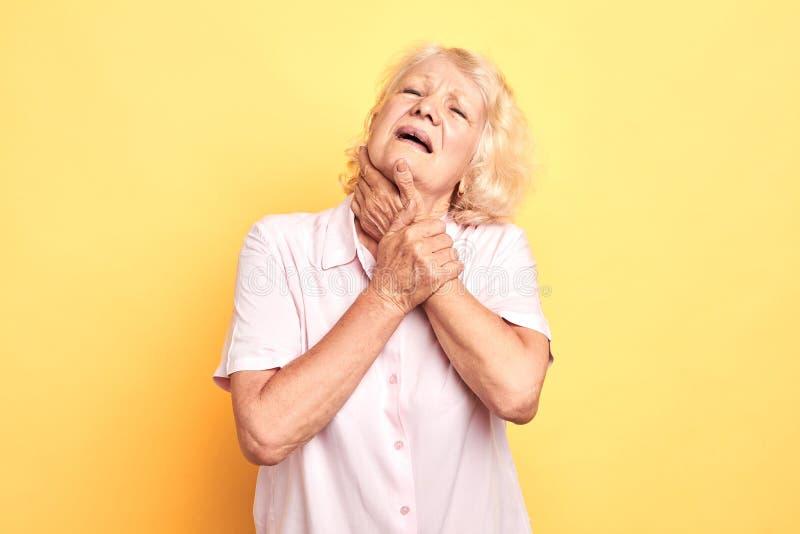 Alte Frau hat Halsschmerzen lizenzfreie stockfotografie