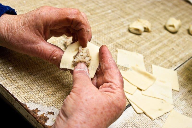 Alte Frau macht traditionelle Mehlklöße lizenzfreies stockfoto
