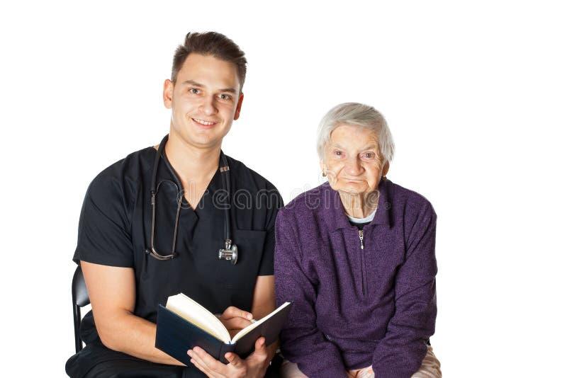 Alte Frau mit dem Betreuer, der einen Roman liest stockfotos