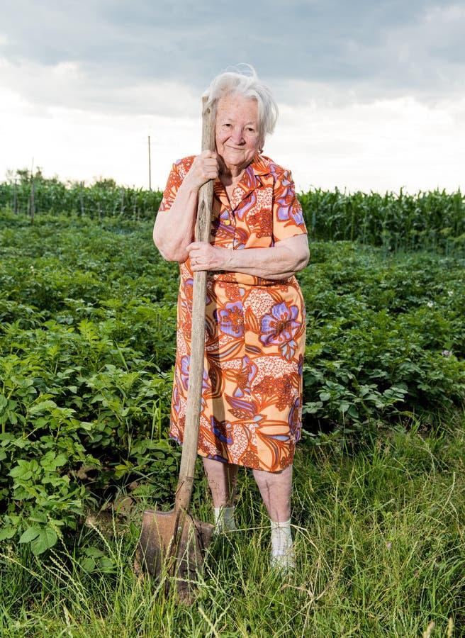 Alte Frau mit einer Schaufel stockfoto