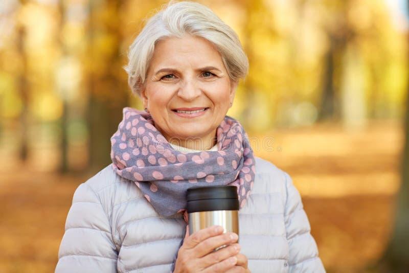 Alte Frau mit heißem Getränk in der Trommel am Herbstpark lizenzfreie stockfotos
