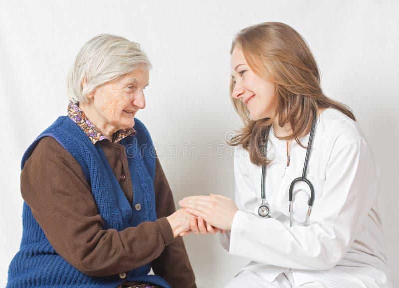 Alte Frau und der süße junge Doktor lizenzfreie stockbilder