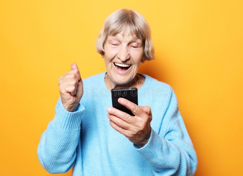 Alte Frau, welche die blaue Strickjacke spricht am Handy trägt lizenzfreies stockfoto