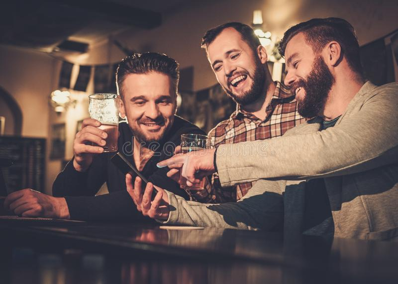 Alte Freunde, die Spaß mit Smartphone haben und Fassbier am Barzähler in der Kneipe trinken lizenzfreies stockbild
