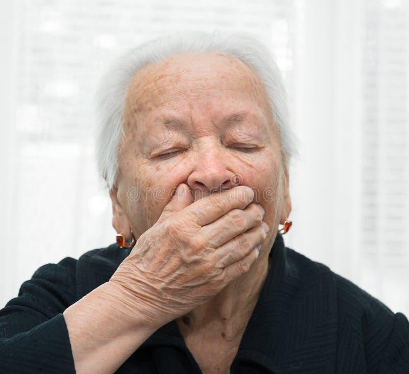 Alte gähnende Frau stockfotografie