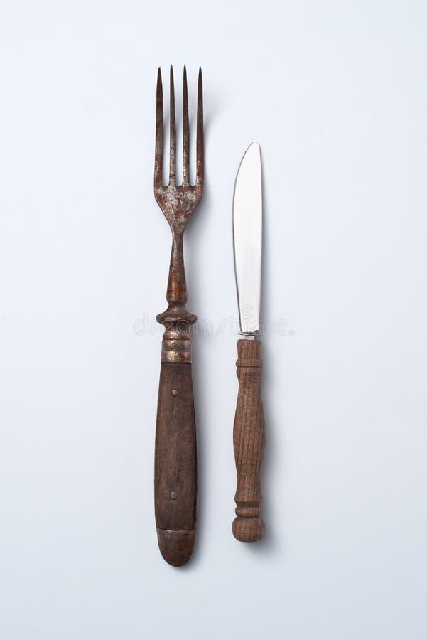 Alte Gabel und Messer mit Holzgriff auf grauem Hintergrund mit Kopienraum Weinlese-Geschirr lizenzfreie stockfotos