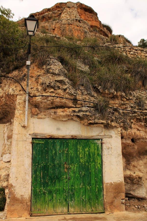 Alte Garage mit der grünen Holztür ausgegraben im Berg lizenzfreies stockfoto
