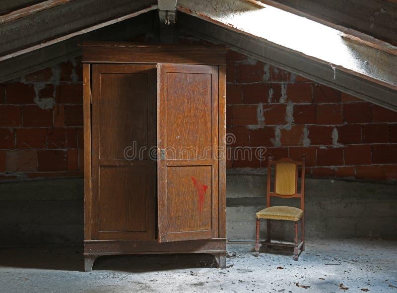 Alte Garderobe und ein Stuhl im unbewohnten Dachboden lizenzfreie stockfotografie