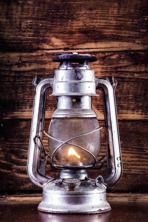 Alte Gaslaterne, die auf Tabelle und hölzernem Plankenhintergrund brennt stockfoto