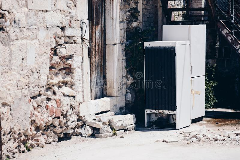 Alte, gebrochene Kühlschränke im Yard eines alten ruinierten Hauses stockbild