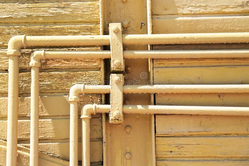Alte gelbe Rohre auf der hölzernen Wand Städtischer Hintergrund Land des Kratzer-Schmutzes Beschaffenheit f?r Ihr Design stockfotografie
