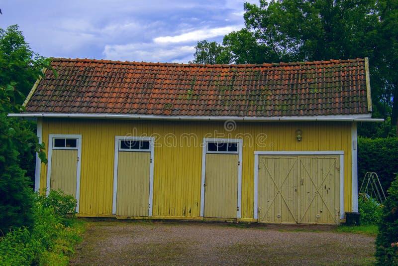 Alte gelbe Scheune mit einem mit Ziegeln gedeckten Dach im Garten lizenzfreies stockfoto