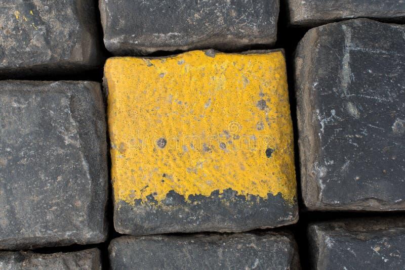 Alte gelbe und schwarze Granitstraßenwürfel oder -kopfsteine als Hintergrund oder Tapete Vertikales Bild stockfotografie