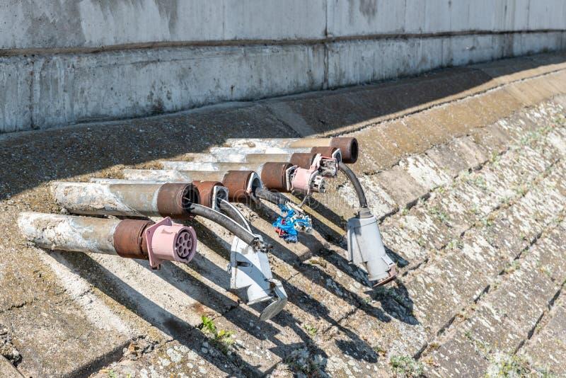 Alte geschädigte Stromleitung des elektrischen Steckers Installationen auf dem Flussufer- oder -ozeanmarinesoldaten für Yachtboot stockbild