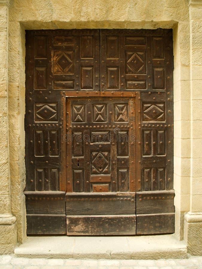 Alte geschnitzte Tür in der Steinwand lizenzfreie stockfotos