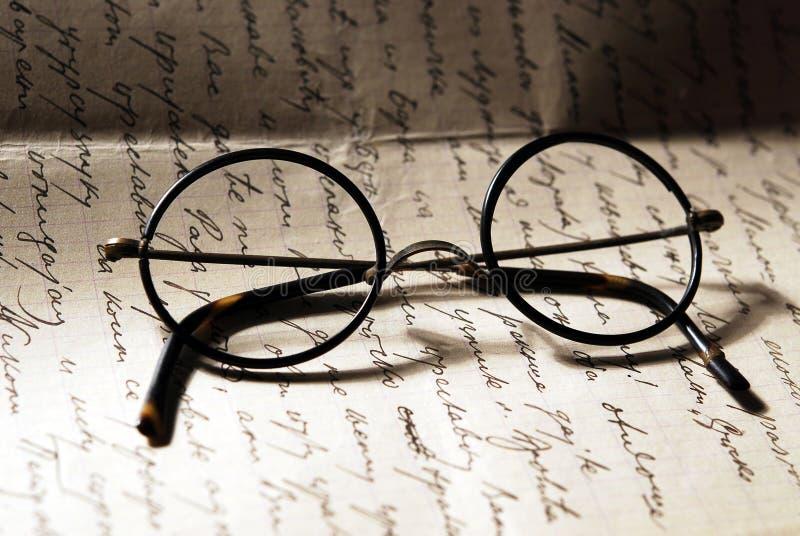 Alte Gläser auf einem Buchstaben lizenzfreie stockfotografie