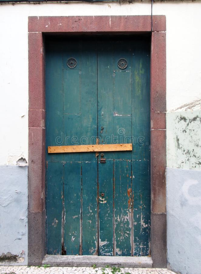 Alte grüne geschlossene Holztür zugeschlossen und abgehalten geschlossen mit Nägeln mit der Schale der Farbe und der roten Einfas lizenzfreies stockbild