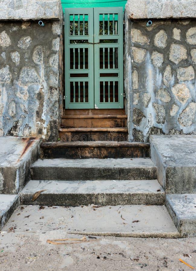 Alte grüne Tür und Steinwand stockbilder