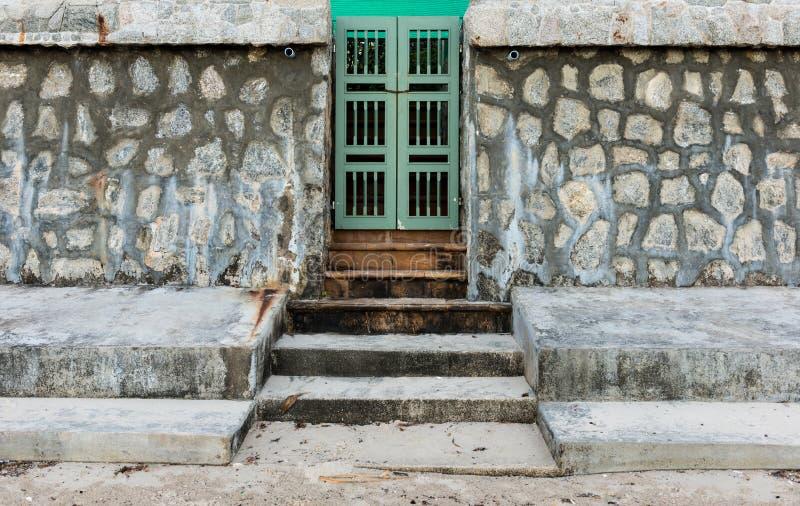 Alte grüne Tür und Steinwand stockfotos