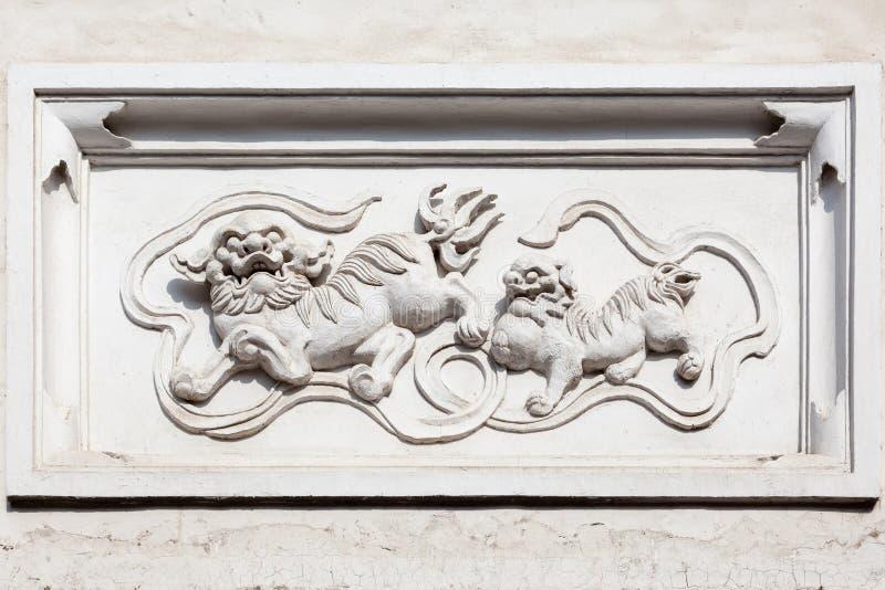 Alte Granitstatue von mythologischen chinesischen Geschöpfen Qilin auf einem im altem Stil Ziegelstein und einer Betonmauer stockfoto