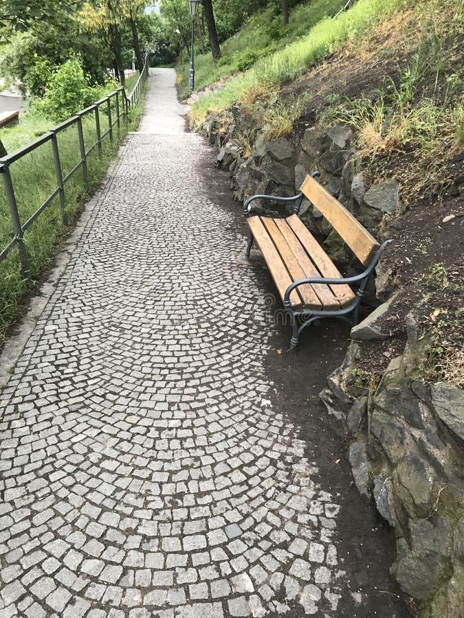 Alte graue Steinstraße und Holzbank lizenzfreie stockfotografie