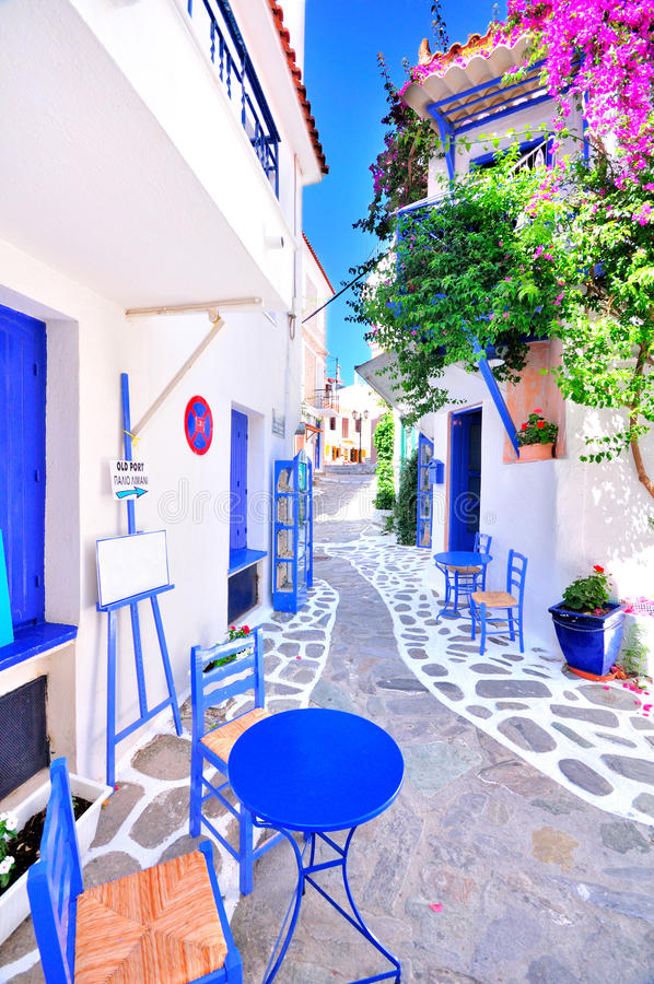Alte griechische Stadt, schmale Straßen, weiße Wände, blaue Möbel und schönes Bouganvilla lizenzfreie stockfotos