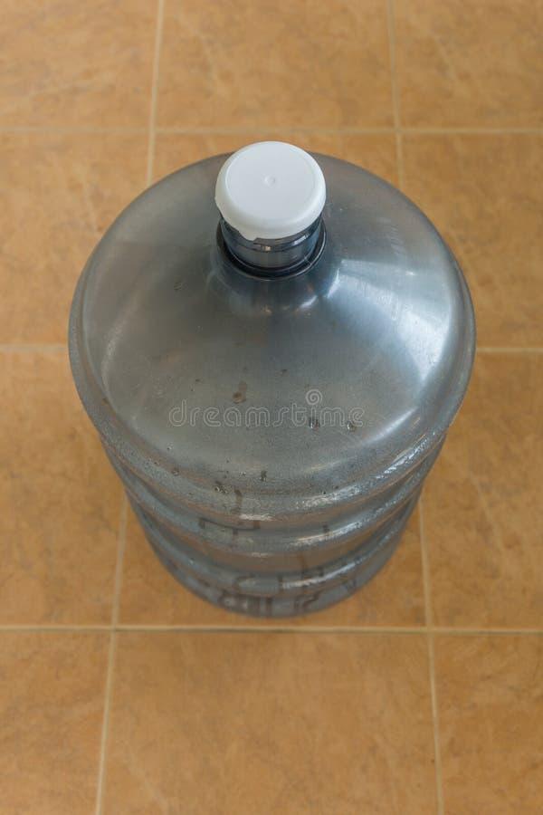 Alte große Flasche Wasser auf dem Boden stockfotos