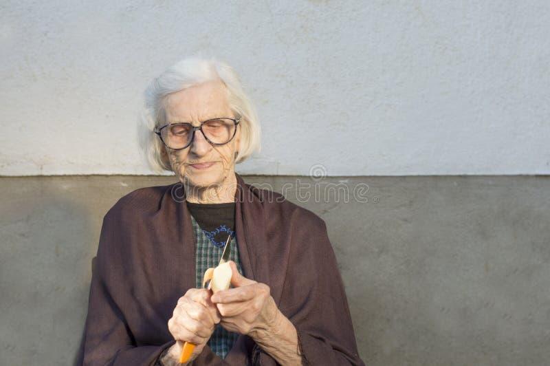 Alte Großmutter, die einen Apfel schneidet und abzieht lizenzfreie stockbilder