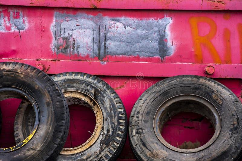 Alte Gummi-LKW-Reifen, die am rosa Metallabfall-Behälter in der Stadt sich lehnen lizenzfreie stockfotos