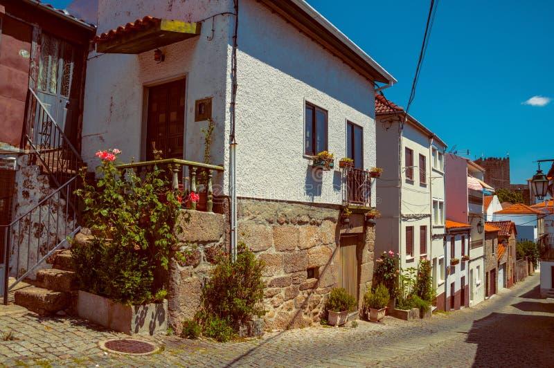 Alte Häuser mit blühenden Töpfen und verlassener Gasse stockbild