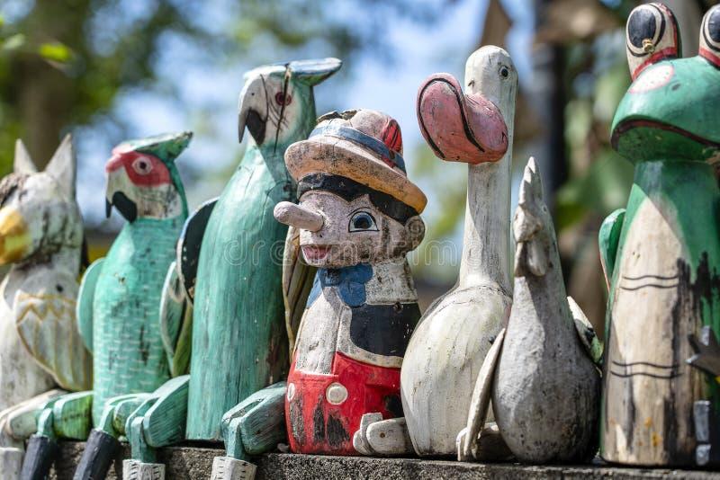 Alte hölzerne Andenkenspielwaren auf dem Steinzaun nahe dem Puppengeschäft in Ubud, Bali-Insel, Indonesien nahaufnahme lizenzfreie stockfotos