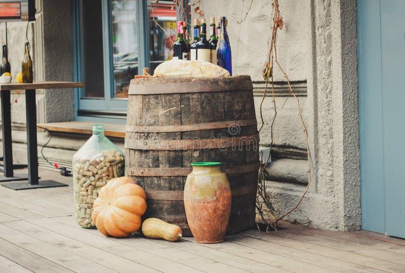 Alte hölzerne Fässer, auf denen es Kürbise und Flaschen gibt lizenzfreie stockfotografie