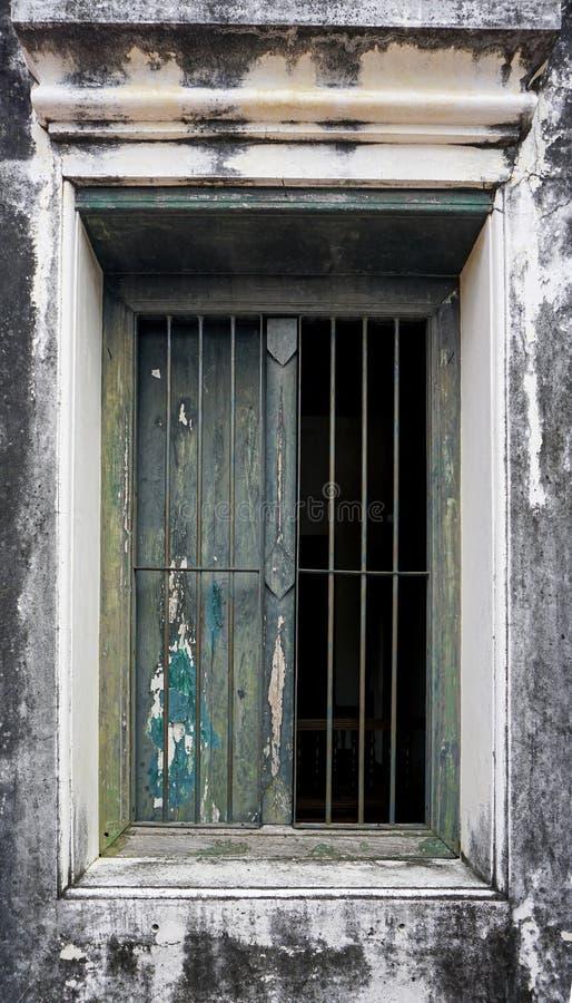 Alte hölzerne Fenster auf alten Gipswänden dort ist ein Stahlschutz gegen Eindringen lizenzfreie stockfotos