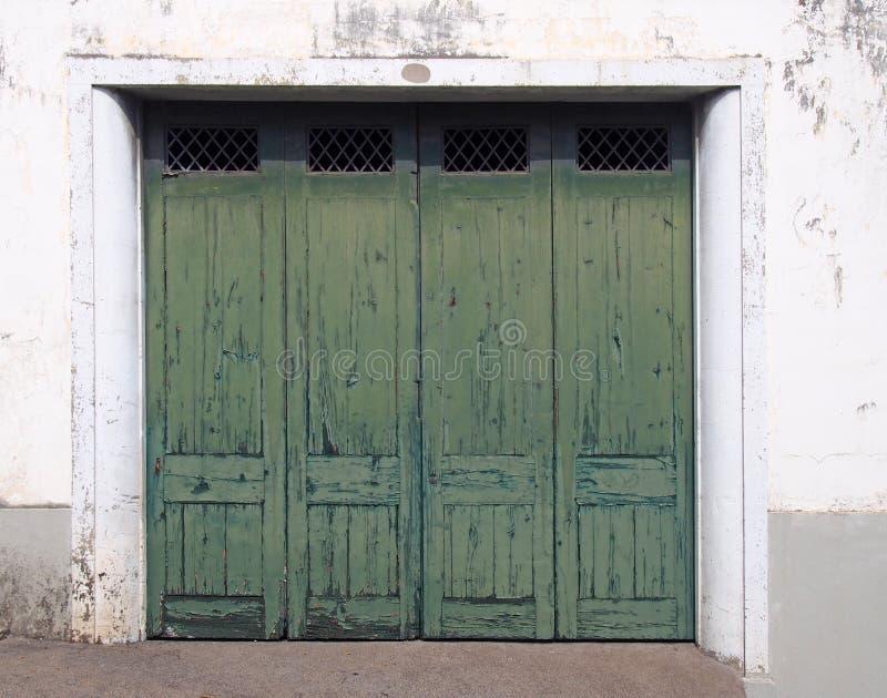 Alte hölzerne getäfelte Außentüren mit grüner verblassender gebrochener Farbe in einem weißen Rahmen und in einer beunruhigten we stockbild