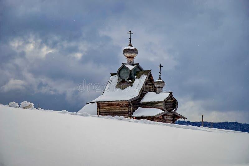 Alte h?lzerne Kirche im Hintergrund von Schneewehen Die Stra?e zur Kirche wird mit Schnee bedeckt stockfotos