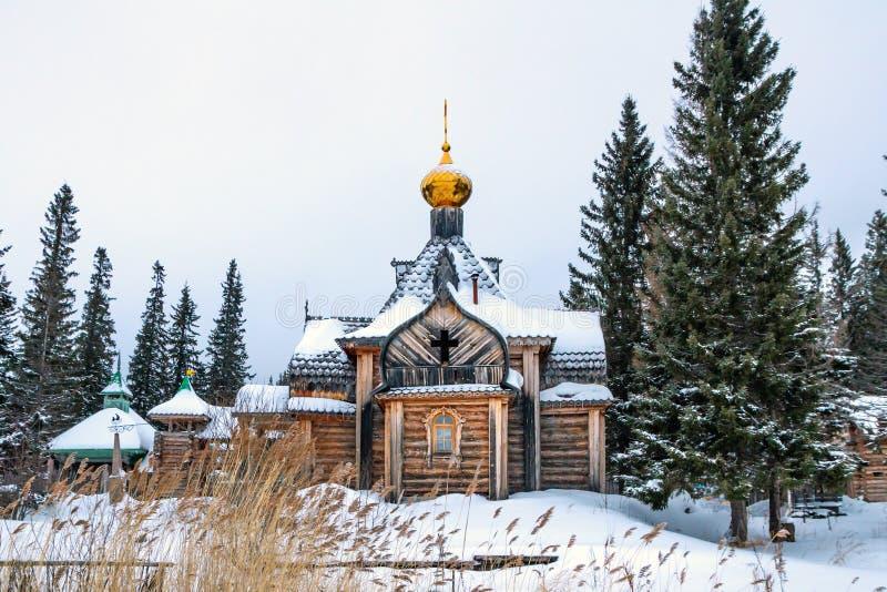 Alte hölzerne Kirche mit Golden Dome und Kreuz, Häuser im Dorf im Winter stockfoto
