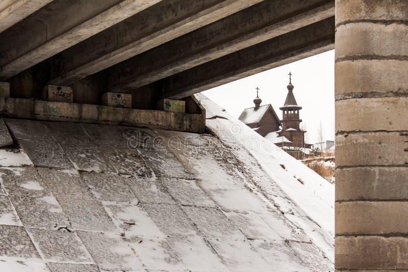 Alte hölzerne orthodoxe Kirche unter einer Brücke stockfotos