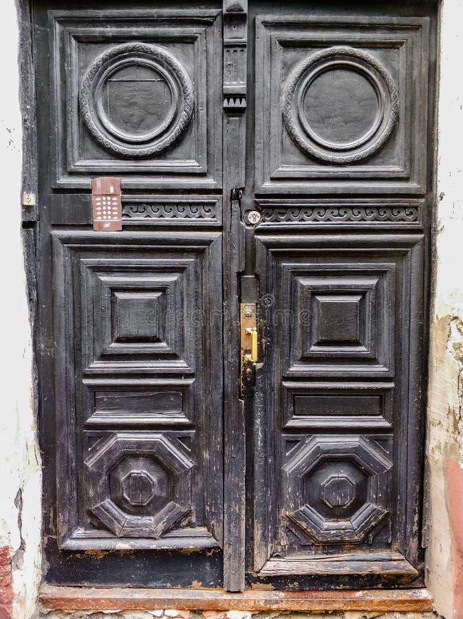 alte hölzerne schwarze Türen mit Einfüllen und Türgriff stockfoto