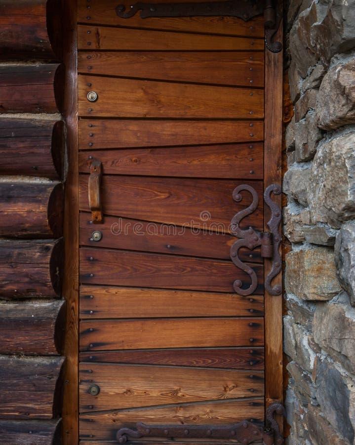 Alte hölzerne Tür mit Steinschlüsselwand lizenzfreie stockbilder