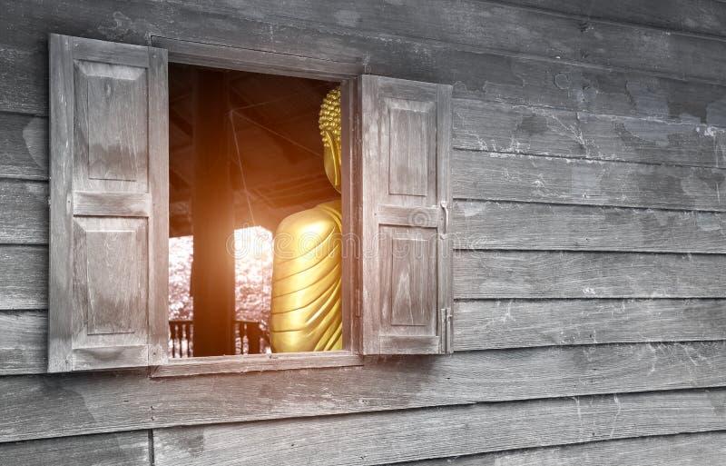 Alte hölzerne Wand mit Fenster nach innen, gibt es einen Buddha, der den Buddha darstellt stockfotografie