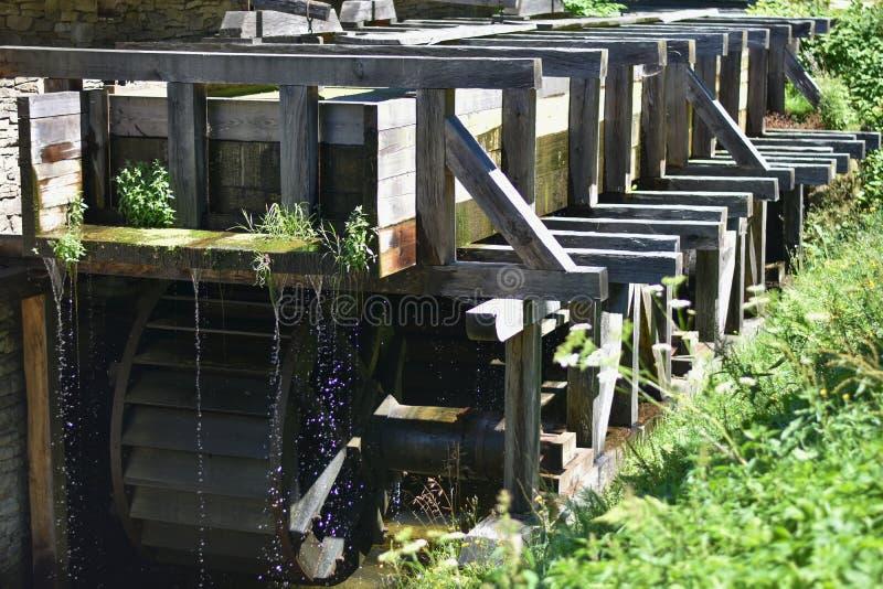 Alte hölzerne Wassermühle im Gras lizenzfreie stockbilder