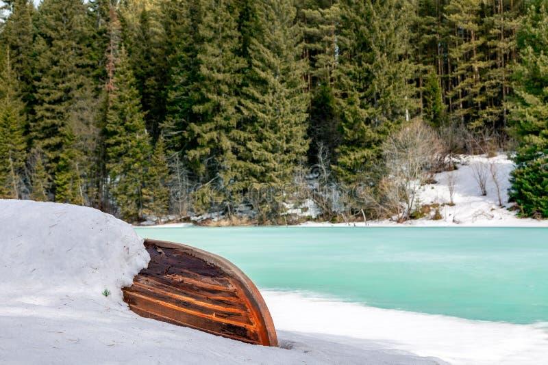 Alte hölzerne zerstörte überschwemmte Fischerbootlüge im Schnee auf Ufer von Eis-bedecktem gefrorenem Fluss im Winterwald, Schnee stockbilder