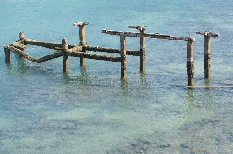 Alte Hafenruinen im blauen Meer stockbilder